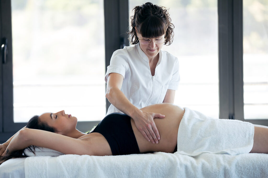 Shot of female physiotherapist massaging tummy on pregnant woman in spa center.